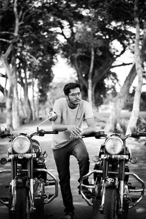 Man in Dress Shirt and Pants Riding Motorcycle in Grayscale Photography