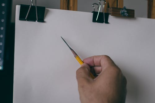A Person Holding a Sharpened Pencil