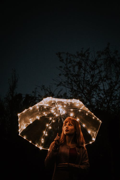 Woman Holding Lit-up Umbrella