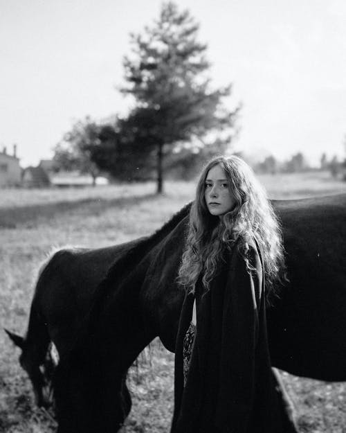 Grayscale Photo of Woman in Black Coat Standing Beside Horse