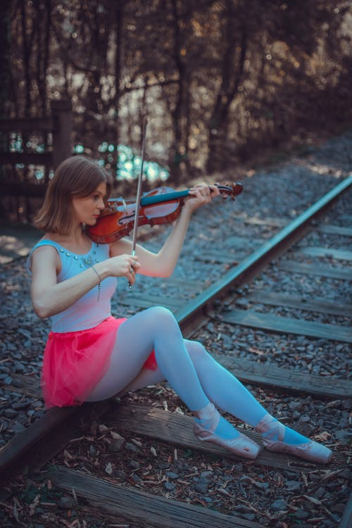 A Woman in a Ballerina Outfit Playing the Violin while Sitting on a Railway Track