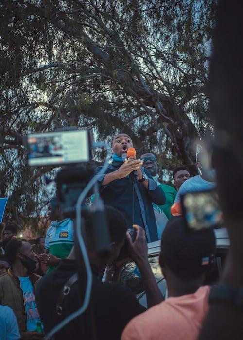 A Man Making a Speech and Talking Through Microphones