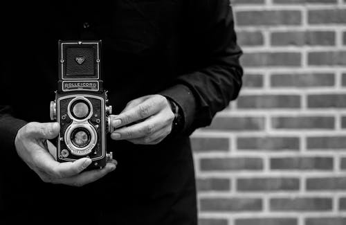 Grayscale Photo of Person Holding Vintage Camera