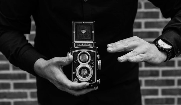 Grayscale Photography of Man Holding Rolleicord Camera