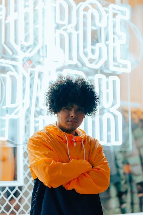 Boy in Orange Hoodie Standing Beside White and Black Wall