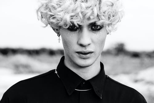 Black and white crop young male with glimmer makeup and dark eyeshadows with curly hairdo looking at camera