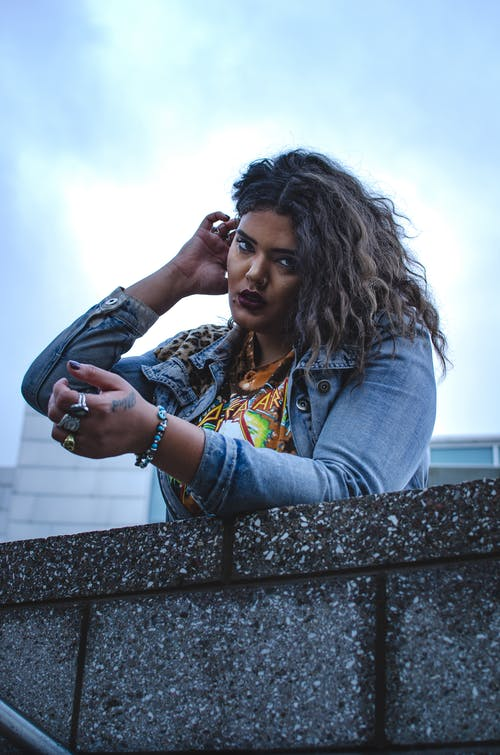 From below of young serious ethnic female in casual clothes leaning on stone barrier in city street under blue sky and looking at camera