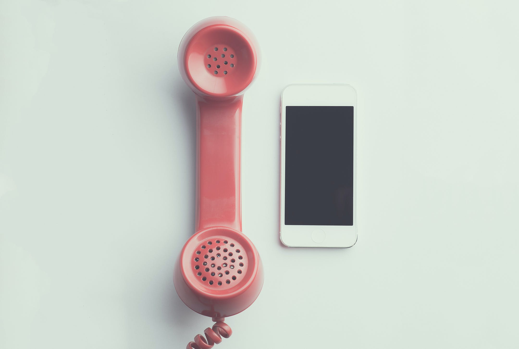 Flat Lay Photography of Red Anti-radiation Handset Telephone Beside Iphone