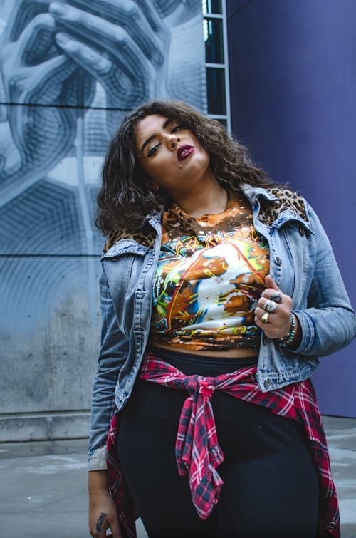 Young confident ethnic plus size lady in casual clothes standing near blue graffiti wall in city street and looking at camera in day