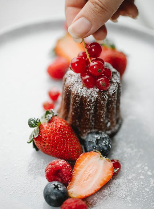 From above of crop anonymous female chef adding berries to cake served on plate with strawberries raspberries and blueberries