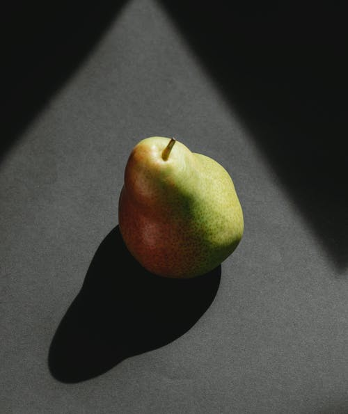 From above of ripe fresh green pear with shadow from daylight on gray background