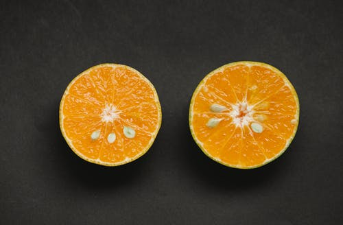 Top view of fresh cut juicy orange with sweet pulp placed on black background