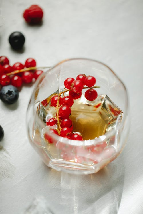 Glass of whiskey with red currant