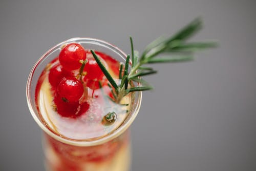 High angle of transparent glass filled with champagne served with fresh red currant and rosemary