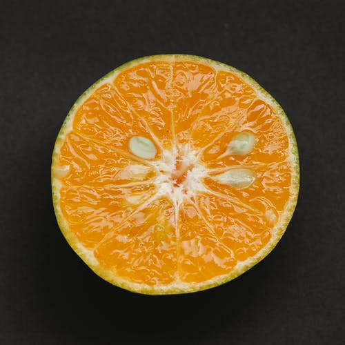 Top view of fresh healthy juicy slice of ripe orange placed on black background