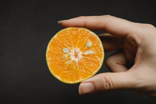Woman showing half of ripe orange