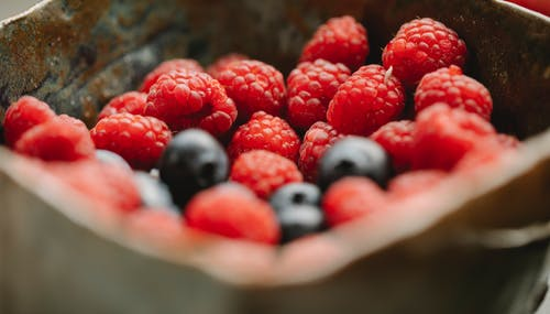Appetizing ripe raspberries and blueberries in bowl