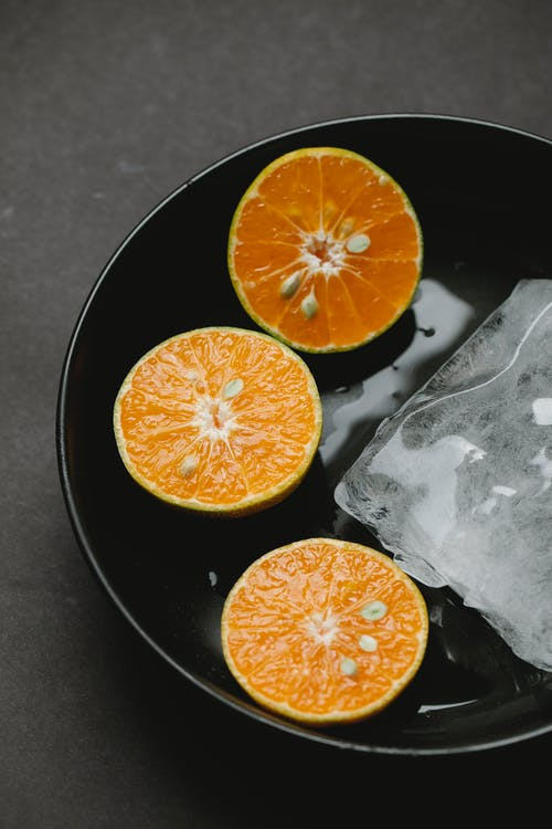 From above of halves of oranges in ceramic bowl with ice representing concept of healthy food