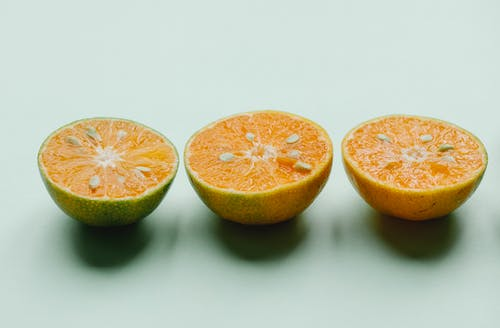 Halves of fresh ripe citruses in row