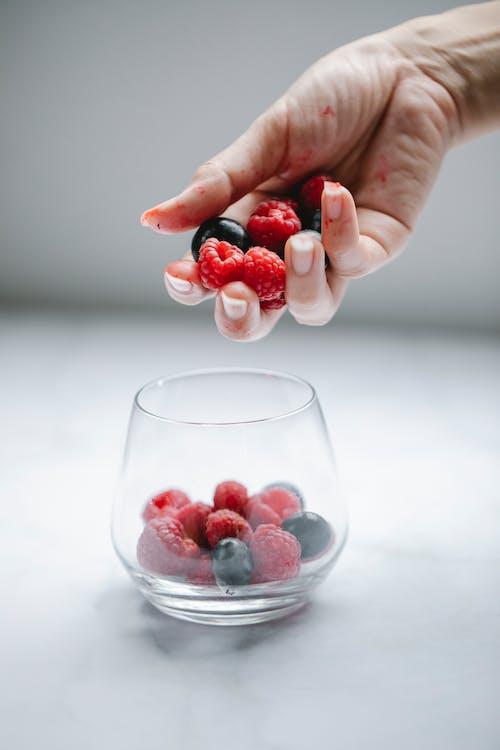 女人把漿果放進玻璃杯