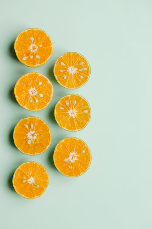 Composition of sliced fresh oranges on green background