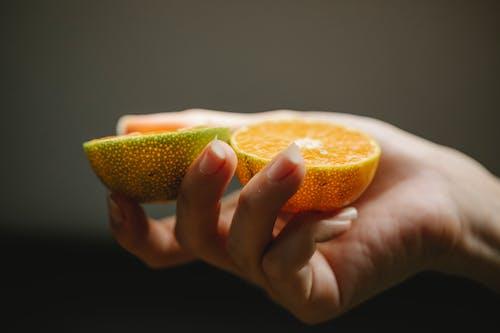 Female with ripe juicy orange containing vitamins