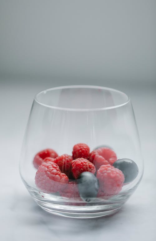 Crystal glass of fresh raspberries and blueberries for healthy nutrition on white table in daylight