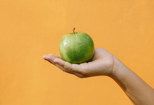 Crop anonymous female demonstrating fruit with thin green skin and crisp flesh against orange background