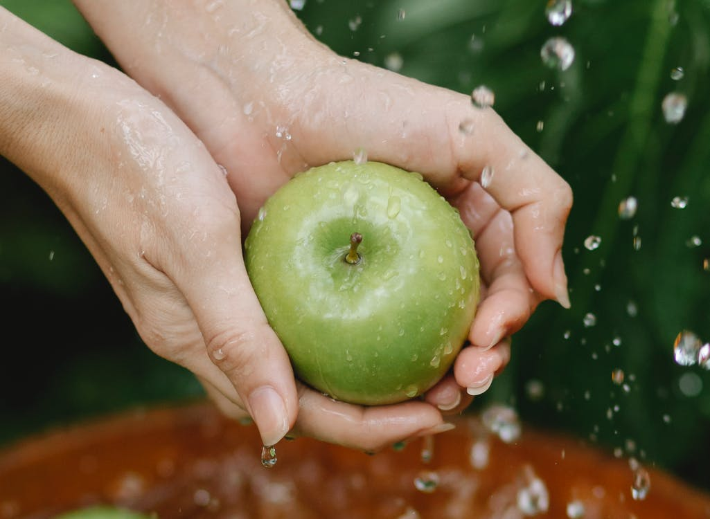 Crop anonymous woman washing green apples in wooden bowl