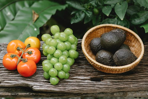 High angle composition of ripe fresh tomatoes green grapes and avocados in wooden bowl placed on bench in lush garden during harvest season