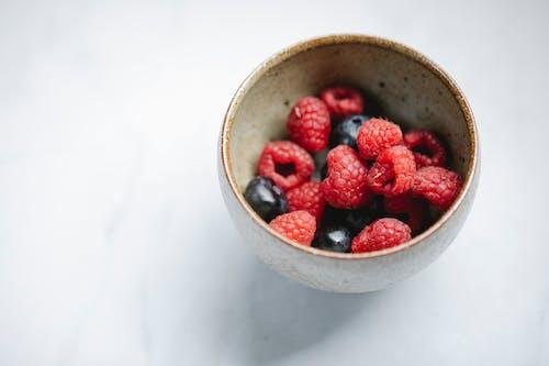 Fresh raspberries and blueberries in bowl