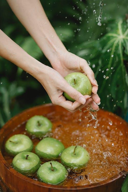 庭の木の洗面器で青リンゴを洗う作物の女性