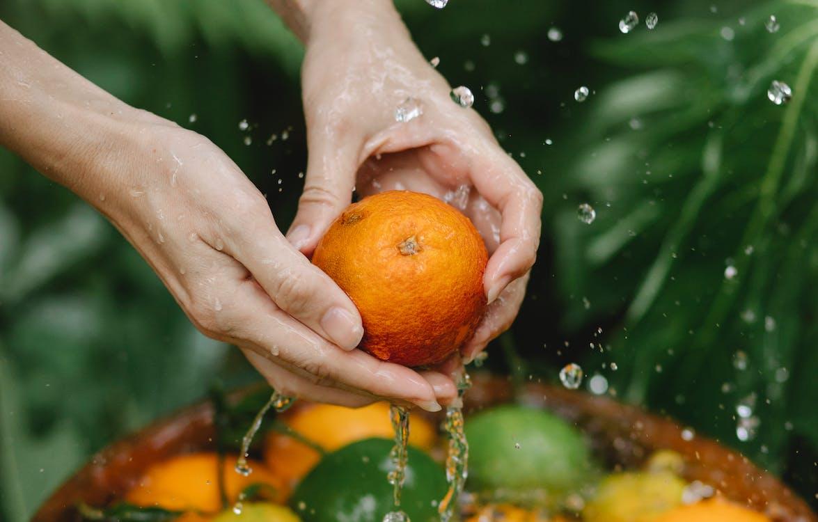 Crop woman washing fresh citruses in tropical garden