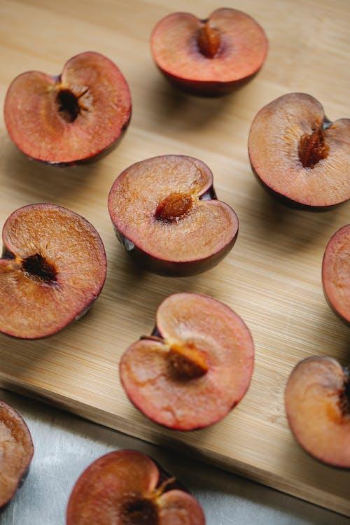 Juicy appetizing halved plums arranged on wooden board