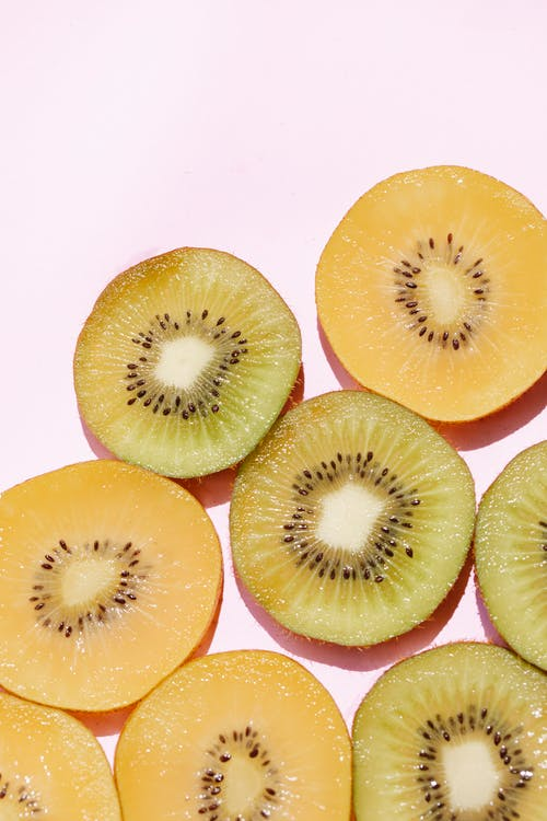 Top view of fresh ripe sliced green and golden kiwis arranged on pink background