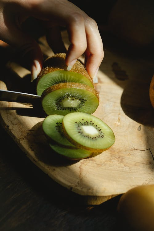 From above of crop anonymous female chopping ripe juicy kiwi with knife in sunny kitchen