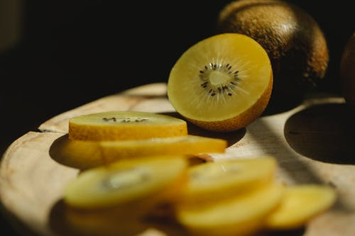 Cut fresh green kiwi with seeds on wooden cutting board in bright sunshine