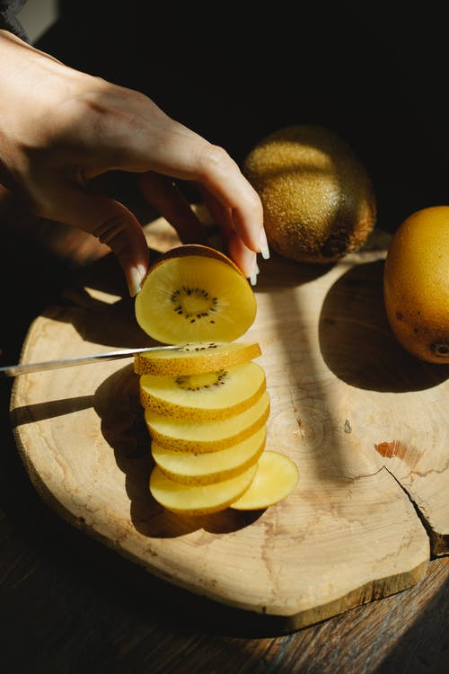 From above crop anonymous female cutting fresh ripe kiwi on wooden chopping board for healthy meal