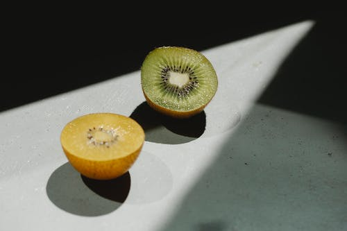 Sliced ripe green and yellow kiwi on table