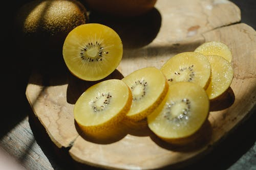 From above of fresh healthy sliced kiwi placed on chopping board in bright rays of sun