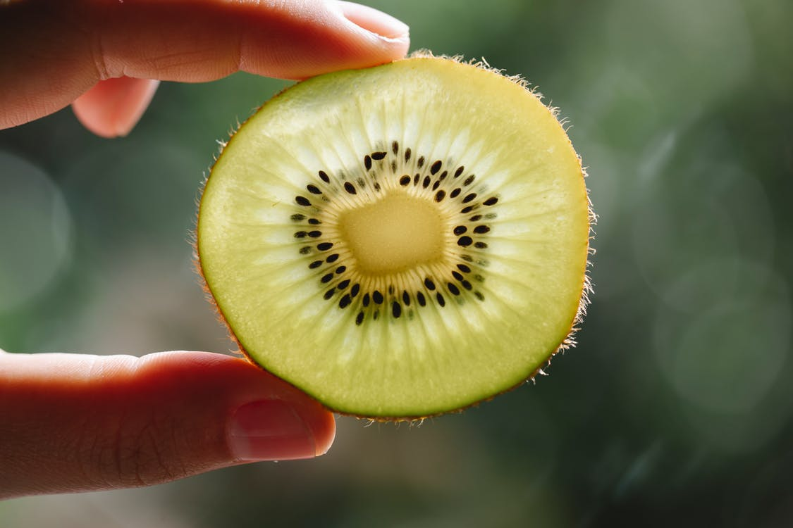 Crop anonymous person demonstrating pulp texture of ripe kiwi with seeds at sunshine