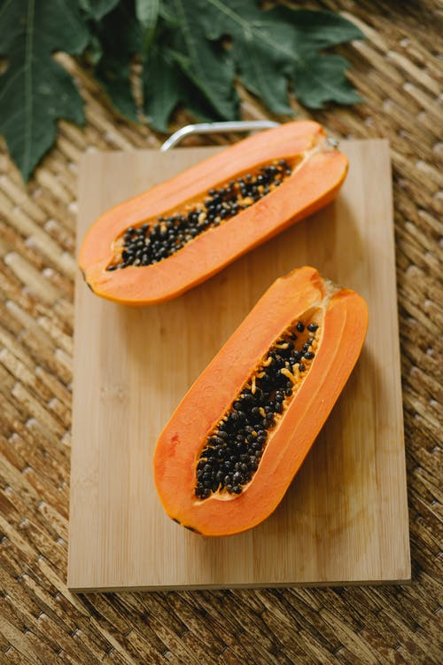 From above of fresh tasty juicy papaya with seeds placed on timber cutting board near green leaves