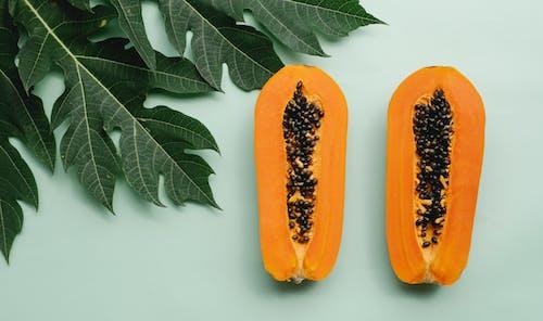 Halves of papaya on green background
