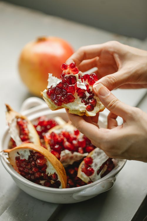 Unrecognizable woman peeling ripe pomegranate with red seeds and putting in bowl on gray table in kitchen