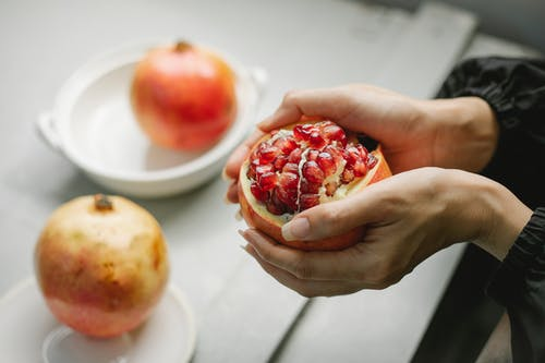Crop woman with peeled pomegranate in hands