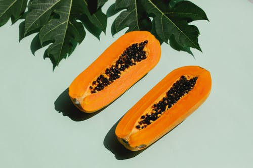 From above composition of green leaves and halved tasty papaya with seeds placed on green background and casting shadow