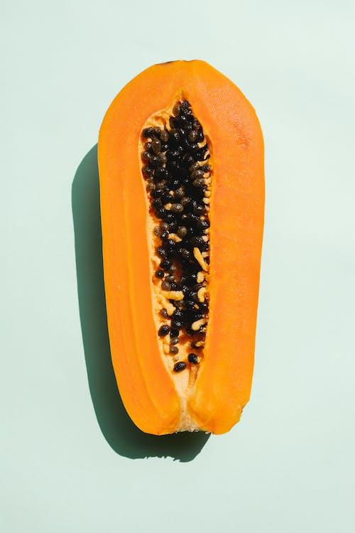 Half of papaya on light background