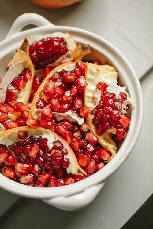 Top view of ripe pomegranate red seeds and peel placed in ceramic pot on table