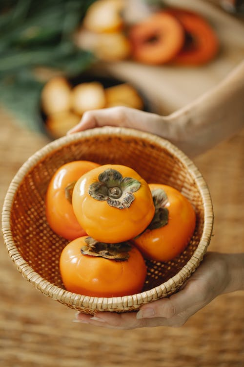 From above of unrecognizable female with heap of ripe orange persimmons placed in wicker bowl with fruits on blurred background