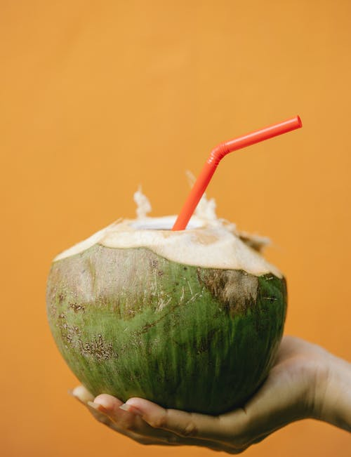 Crop woman with coconut cocktail